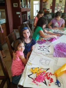 My girls at a friend's house, doing crafts. Fiala has the blue headband, and Audrey is in the background, top left.